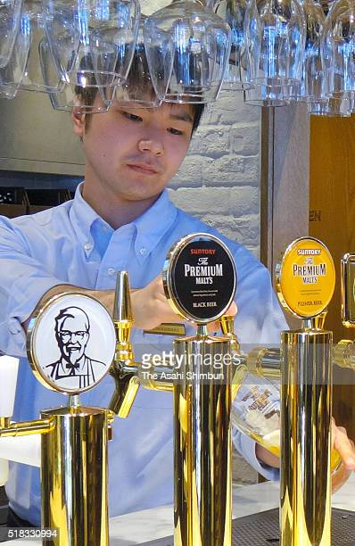 A staff serves beer at the Kentucky Fried Chicken Japan Ltd Takadanobaba outlet during a press preview on March 25 2016 in Tokyo Japan KFC...