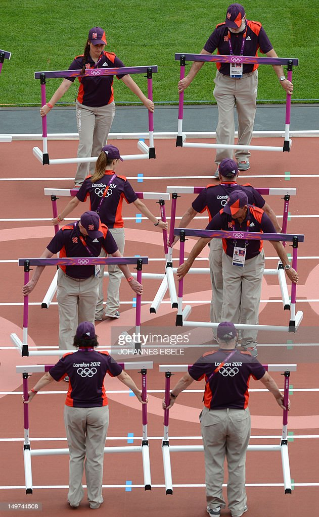 Staff set up hurdles during the athletic : News Photo