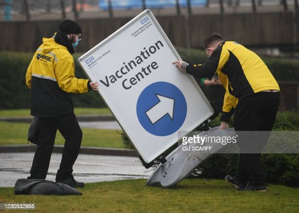 Staff set up signage as people arrive at the Etihad tennis centre as it opens as a mass vaccination centre against the coronavirus in Manchester,...