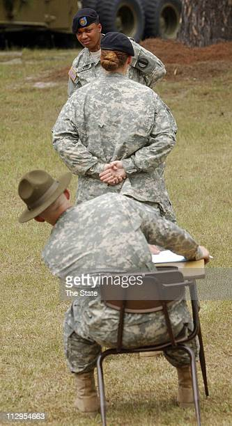 Staff Sgt Rhonda Boatwright rear cheks with instructor Staff Sgt Edwin Justed while being tested on issuing instruction to another candiate posing as...
