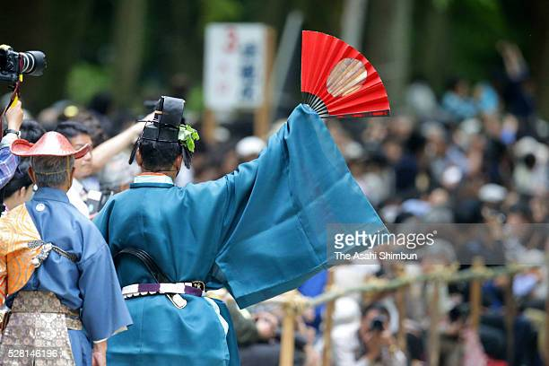 A staff signs to next archer during the 'Yabusame' horseback archery ritual at Shimogamo Jinja Shrine on May 3 2016 in Kyoto Japan