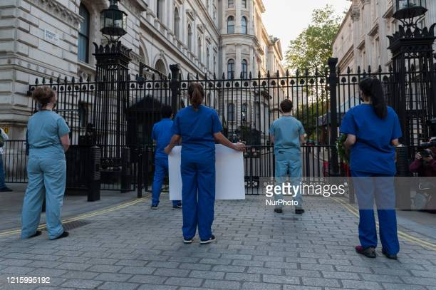 Staff stage a silent protest outside the gates of Downing Street during the weekly 'Clap for our Carers' applause for the NHS and key workers on the...