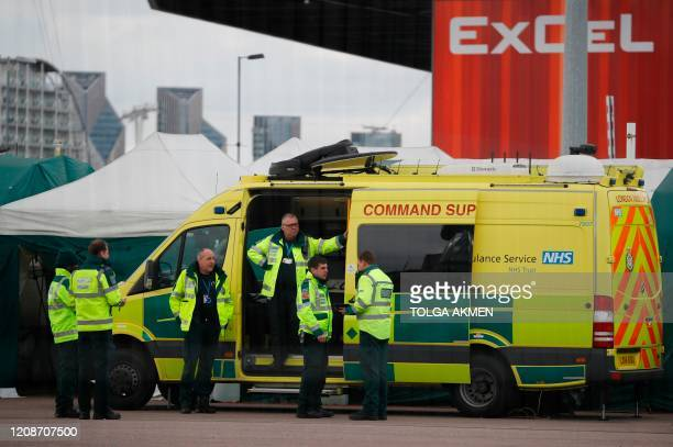 Staff stand by a London Ambulance Service Command Support vehicle parked outside the ExCeL London exhibition centre in London on March 31 where the...