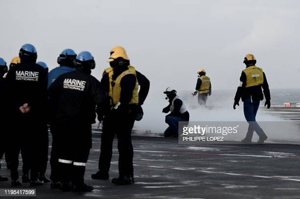 Staff stand on the deck as Rafale jet fighters take off the French aircraft carrier Charles de Gaulle at sea off the coast of the city of Hyeres on...