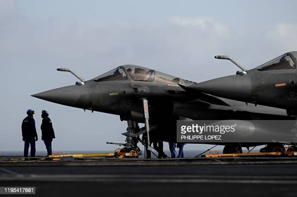 Staff stand on the deck past Rafale jet fighter on the French aircraft carrier Charles de Gaulle at sea off the coast of the city of Hyeres on...