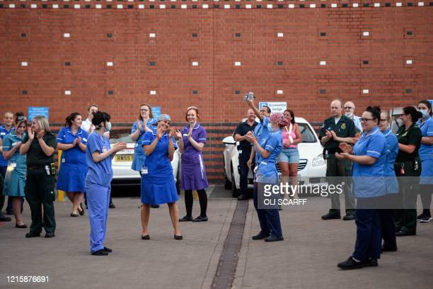 """Staff take part in a national """"clap for carers"""" to show thanks for the work of Britain's National Health Service workers and frontline medical staff..."""