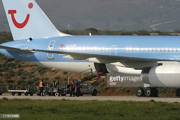 Staff unloads luggage from the British Boeing 757-200 operated by Thomson Airways at Athens International airport in Spata on April 4 after an...