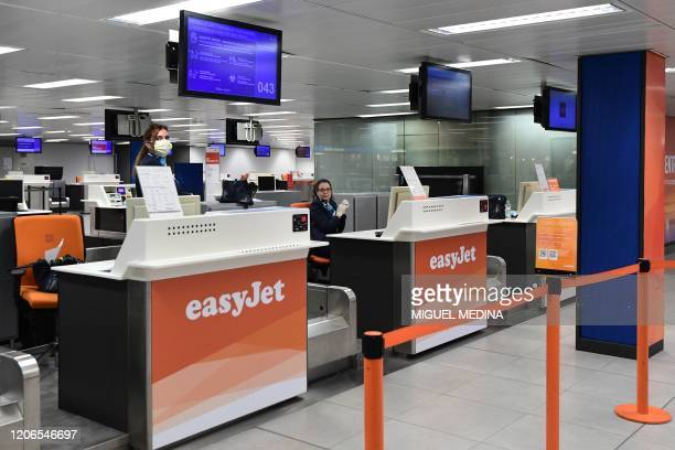 Staff wait at an easyJet check in counter at Milan's Linate airport on March 11 a day after Italy imposed unprecedented national restrictions on its...