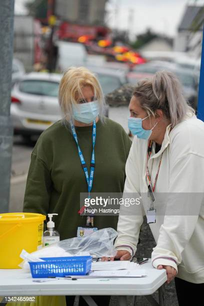 Staff wait for people to attend an NHS walk-up vaccination unit outside the village hall on September 25, 2021 in the village of Summercourt, near...