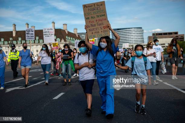 Staff walk over Westminster Bridge from St Thomas' Hospital to Downing Street as they demand a pay rise on July 29, 2020 in London, England. Almost...