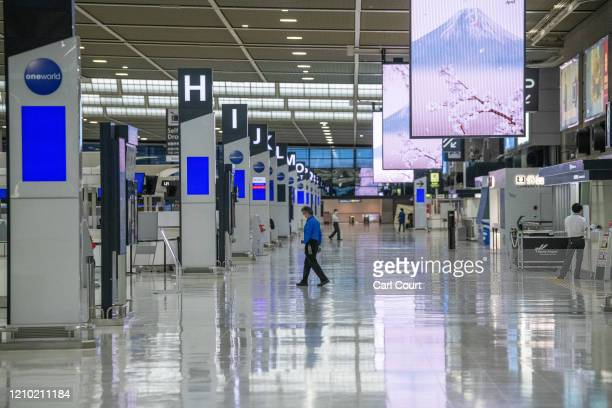 Staff walk through a near empty terminal at Narita Airport on April 17, 2020 in Tokyo, Japan. Narita Airport, one of Japans busiest, has closed one...