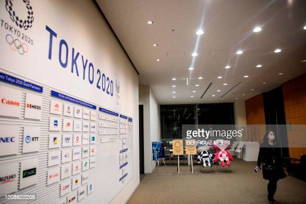 A staff walks past the Tokyo 2020 Olympic and Paralympic Games mascots Miraitowa and Someity after a press conference at the Tokyo 2020 headquarters...