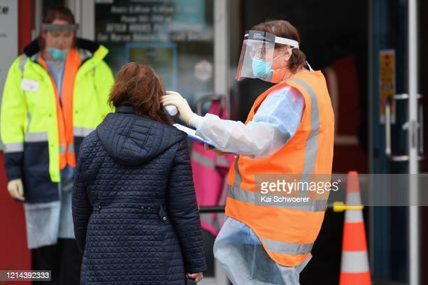 Staff wearing personal protective equipment check the temperature of patients in front of a medical centre on March 24, 2020 in Christchurch, New...