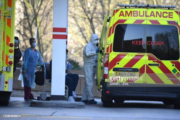 Staff wearing personal protective equipment help a patient into an ambulance at St Thomas' Hospital in London on March 24 2020 Britain's leaders on...
