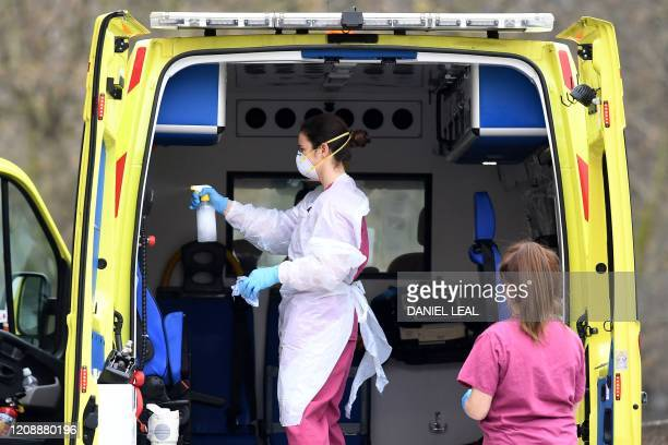 Staff wearing PPE of gloves and face masks as a preactionary measure against COVID19 disinfect an ambulance after it arrived with a patient at St...