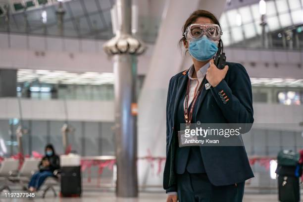 MTR staff wearing protective goggles and mask stands by in the departure hall at Hong Kong High Speed Rail Station on January 29 2020 in Hong Kong...