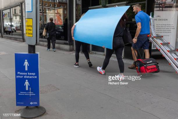 Staff with visual merchandising supplier 'Bright Leaf' carry blue boards and materials back to their West End premises, on 24th July 2020, in London,...