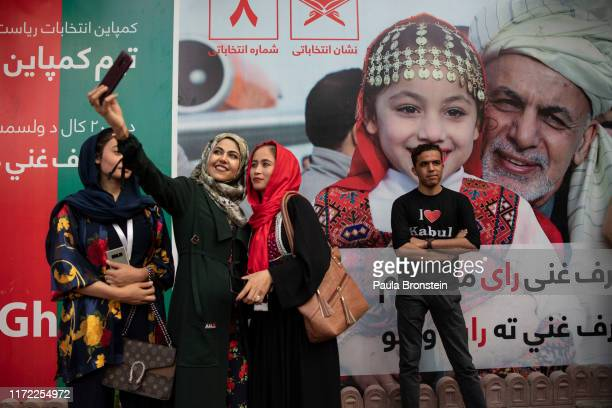 Staff workers on President Ghanis election campaign take a selfie next to a Ghani election billboard during a staff post election party at the Ghani...