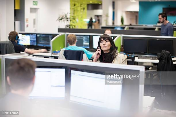 Staff working on computers in office cubicles with woman on the phone