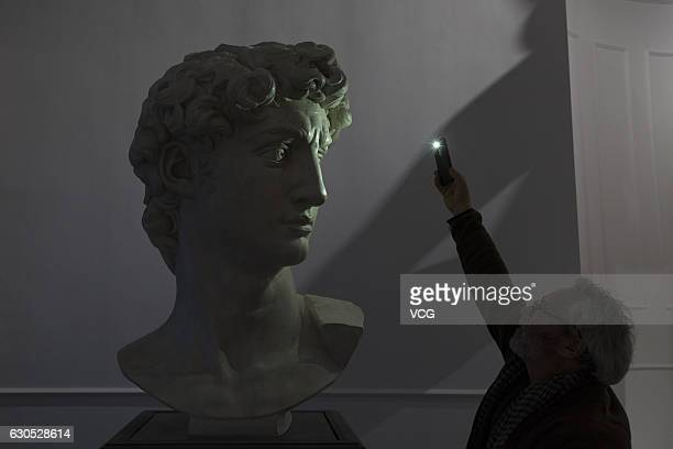 """Staff works on the lighting for the exhibition """"The Divine Michelangelo"""" at Shanghai Modern Art Museum on December 25, 2016 in Shanghai, China...."""
