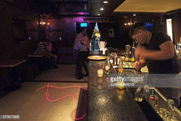 A staffer cleans a bar in eastern Caracas on March 11 2014 Riots tear gas pellets and burning barricades are dousing the nightlife in the bars...