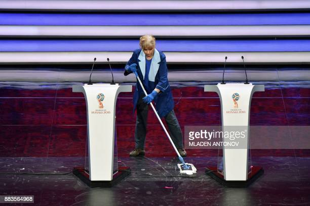 A staffer cleans the stage prior to the final draw for 2018 FIFA World Cup football tournament at the State Kremlin Palace in Moscow on December 1...