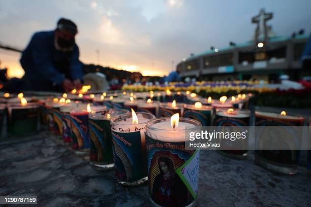 Staffer of the Basilica of Guadalupe lights candles with messages placed by Catholics in the days prior to the celebration in the central area of the...