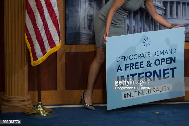 A staffer removes a 'net neutrality' sign after a press conference following the vote that would help stop the Federal Communications Commission's...