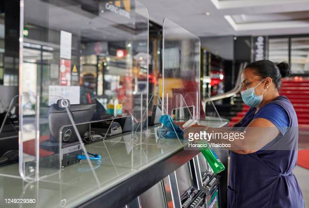 Staffer wears protective mask as she disinfects the plexiglass panels at the information counter in the gaming area of the Casino Estoril, a spot...