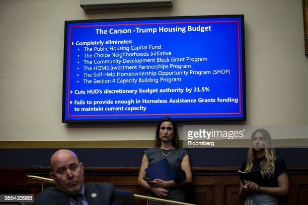 Staffers stand below a slide of the CarsonTrump housing budget displayed as Ben Carson secretary of Housing and Urban Development not pictured...