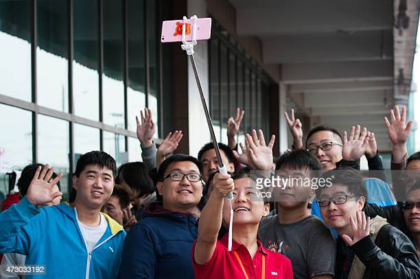 Staffs and customers take a selfie before the high configuration Xiaomi Note to be on sale at a Xiaomi experience store on May 12 2105 in Beijing...