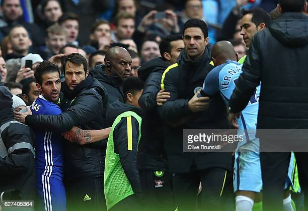 Staffs and offiicials try to separate Fernandinho of Manchester City and Cesc Fabregas of Chelsea after Fernandinho pushes down Fabregas during the...
