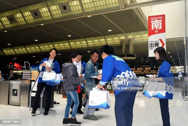 Staffs distribute gifts to passengers as they mark the 40th anniversary of the airport opening at Narita International Airport on May 20 2018 in...