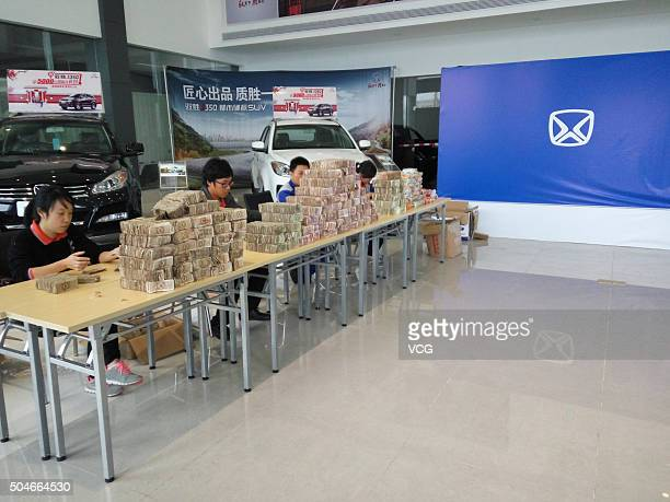 Staffs of a 4S store count the cash brought by a citizen who saves 100000 yuan notes to buy a van at a 4S store on January 11 2016 in Zhanjiang...