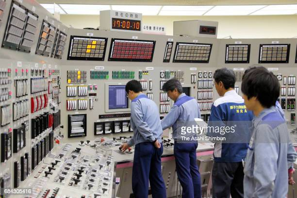 Staffs of the Kansai Electric Power Co's Takahama Nuclear Power Plant restart its No 4 reactor at the central control room on May 17 2017 in Takahama...