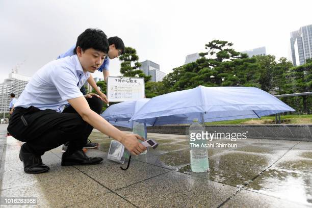 Staffs of the Tokyo Metropolitan Government check the temperature after sprinkling water on a footpath on August 13 2018 in Tokyo Japan