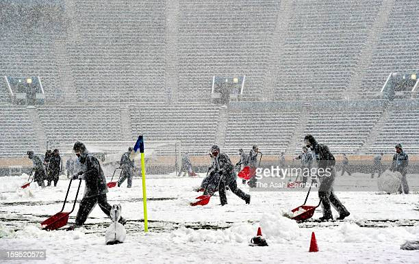 Staffs try to remove snow on the pitch in preparation for the All Japan High School Football Championship Final at the National Stadium on January 14...