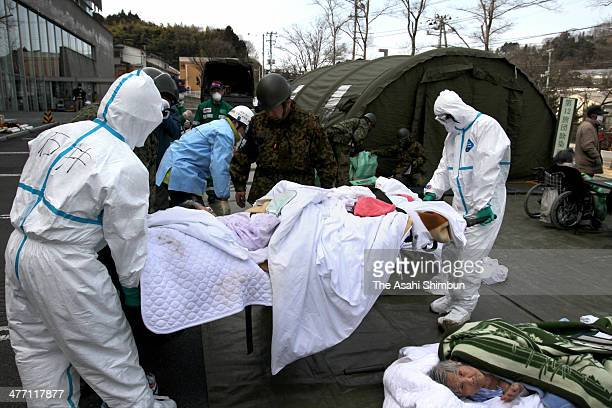 Staffs wearing radiation protection gears carry possible radiation exposed patients at an evacuation center after Fukushima Daiichi Nuclear Power...