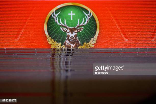 A stag logo sits on boxes for Jaegermeister fruit liquor on the packing production line inside the MastJaegermeister SE bottling plant in...