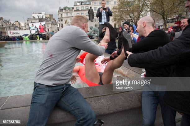 Stag party humiliation pranks as the groom is dressed up as a woman in an orange dress and wig then pushed into the fountains in Trafalgar Square in...