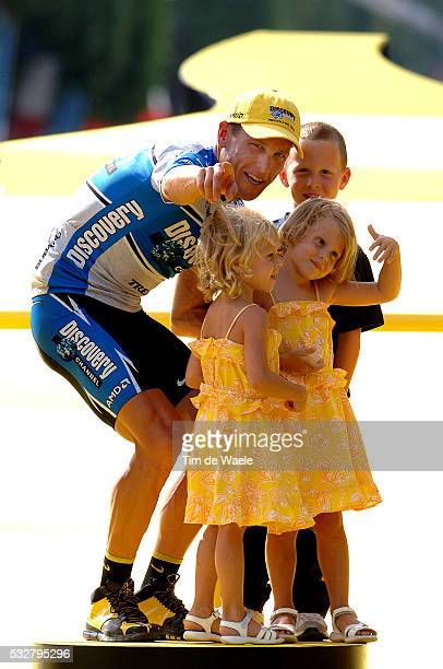 Stage 21 CorbeilEssonnes Paris Lance Armstrong sporting the yellow jersey stands with his children Luke Grace and Isabella on the victor's podium...
