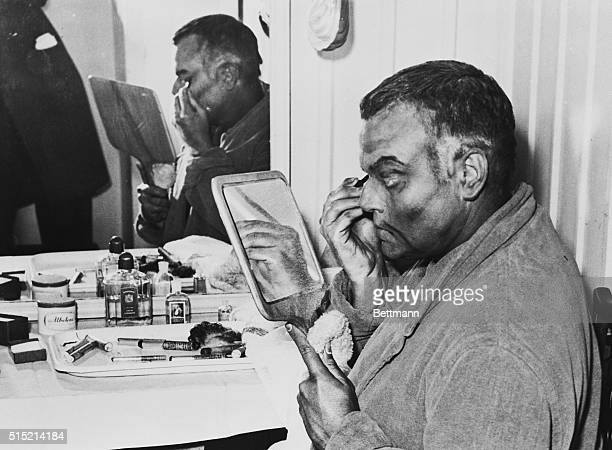 Stage and movie actor Orson Welles puts on stage makeup for his part as Othello in the play Othello by Shakespeare at the St James Theatre in London...