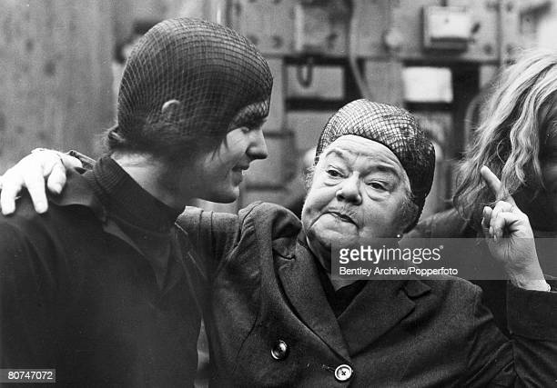 August 1970 Coronation Street star Violet Carson dressed as her character Ena Sharples pictured with a long haired worker at a northern factory near...