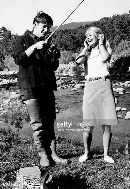circa 1965 British actor Tom Courtenay pictured with costar Julie Christie who enjoys a laugh at his expense as his fishing line becomes tangled The...