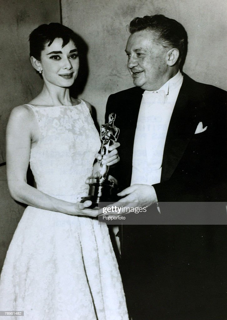 """Stage and Screen. Personalities. pic: March 1954. Actress Audrey Hepburn receives her Oscar as Best Actress for her part in the film """"Roman Holiday"""" from actor Jean Hersholt. Audrey Hepburn, (1929-1993) born in Brussels, a truly international star from a  : News Photo"""