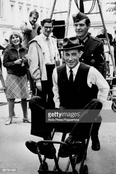 May 1966 British actor Tom Courtenay pictured pushing actor Peter O'Toole in a whellbarrow during filming of The Night Of The Generals