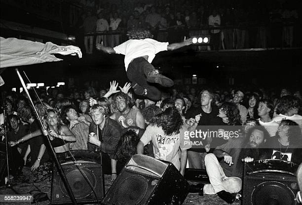 Stage diver launches himself into the crowd from the stage at a rock gig WAustralia 1990s