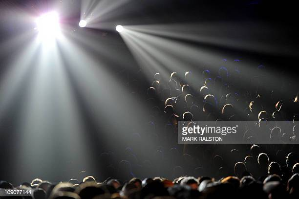 Stage lighting radiats on the audience as they listen to rap star Eminem perform with Rihanna onstage during the GRAMMY Awards Show at the Staples...