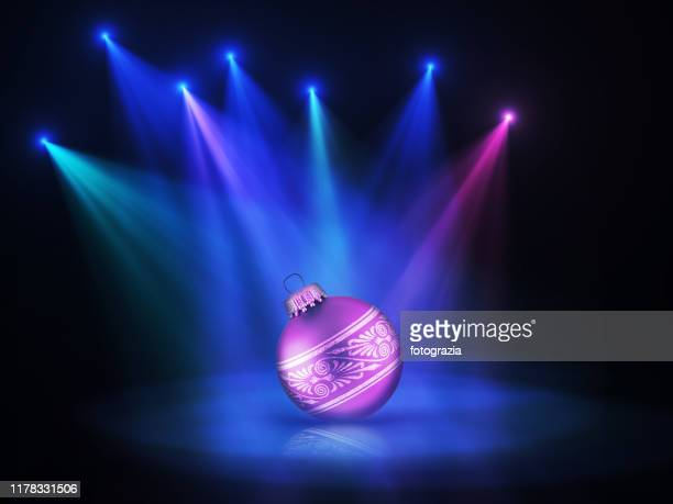 stage lights illuminating a christmas ornament - stage performance space stockfoto's en -beelden