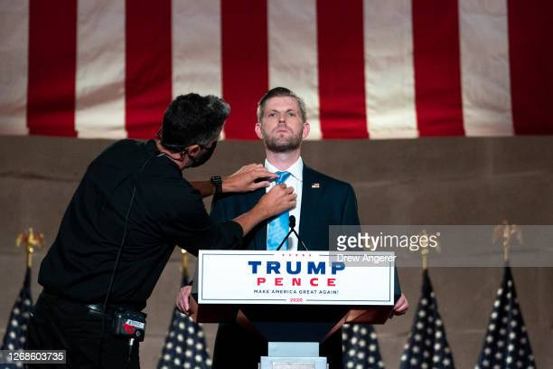 A stage manager adjusts the tie of Eric Trump son of US President Donald Trump before he prerecords his address to the Republican National Convention...